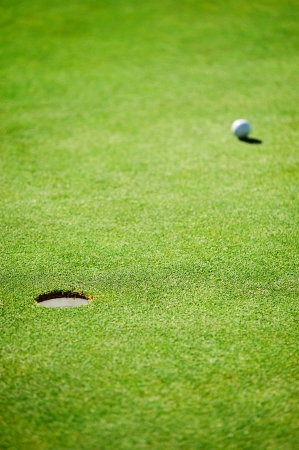 golf ball and hole on green heading towards the cup photo
