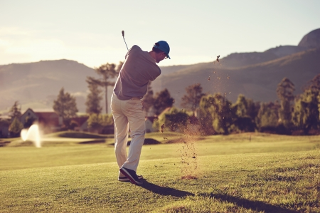 Golfer hitting golf shot with club on course while on summer vacation photo