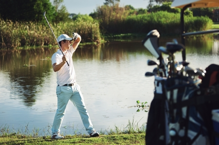 blinded: golf man shields eyes from sun to see where ball is. real golfer playing game