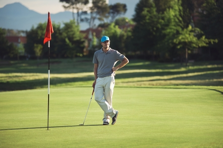 stance: relaxed golfer standing on green with putter at sunset while playing 18th hole