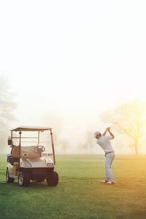 golf cart: golf man at sunrise playing shot from fairway with cart nearby Stock Photo