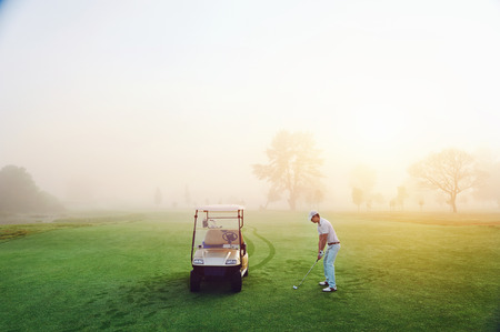playing golf on the fairway with cart in the morning sunrise and misty dew grass photo