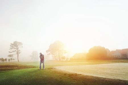 columpios: Golfista de astillado en el verde en la salida del sol sobre el campo de golf en condiciones brumosas