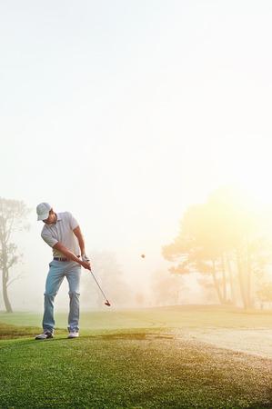 골프를 치는 사람은 안개 낀 상태에서 골프 코스에서 일출 녹색에 치핑