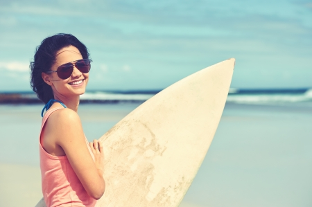surfboard: Portrait of happy young woman with surfboard at the beach