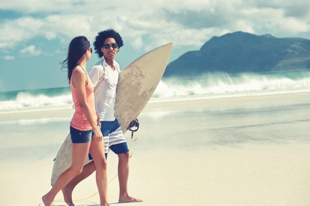 Hispanic couple walk on beach together with surfboard having fun outdoors photo