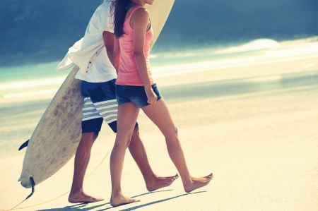 watersports: Hispanic couple walk on beach together with surfboard having fun outdoors