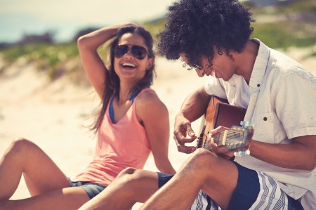 guitarra: Linda pareja hispana, tocar la guitarra serenatas en la playa en el amor y abrazar