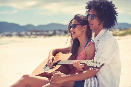 hispanic women: Cute hispanic couple playing guitar serenading on beach in love and embrace
