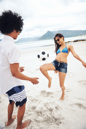 beach ball girl: Latino couple playing soccer on beach with ball kicking and having fun Stock Photo