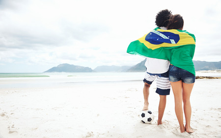 Brazil soccer fans stand on beach together with flag  with ball