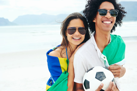 Portrait of latino couple with Brasil flag and soccer ball