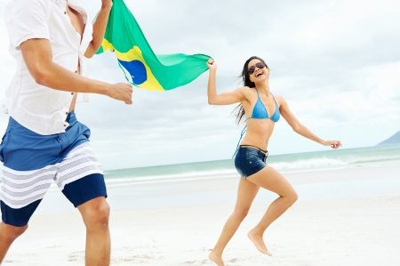 brazil beach: Latino hispanic couple are Brasil fans and hold flag having fun together