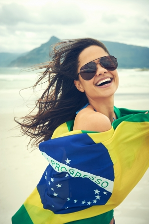 brazil beach swimsuit: Latino woman with Brasil flag laughing and smiling in support of Brazilian soccer fan