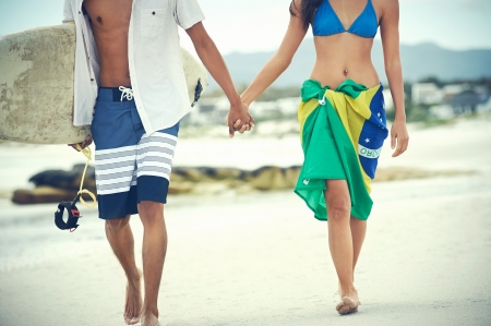 Brasil latino hispanic couple walking holding hands with surfboard and flag as sarong photo