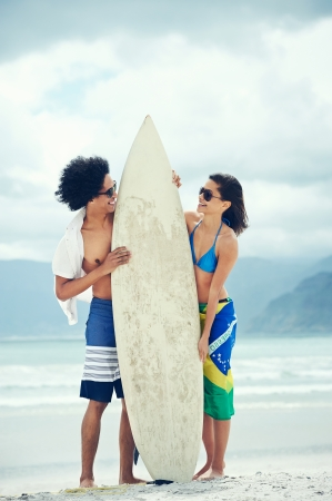 Couple having fun together at the beach with surfboard and brasil flag photo
