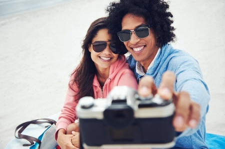 dating and romance: couple taking selfie self portrait at the beach with retro hipster camera