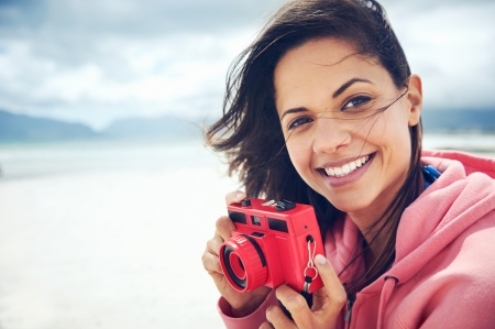 cool girl: Portrait of beautiful Latino woman with retro hipster camera having fun at the beach