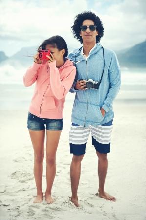 Fashionable hipster couple taking retro camera photo at beach photo
