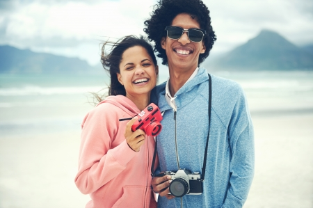 Pareja que se divierten haciendo fotos con c�mara retro inconformista de la vendimia en la playa photo