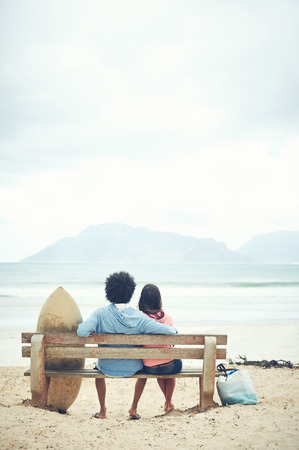 sitting on a bench: Couple sitting on bench together at the beach in love Stock Photo