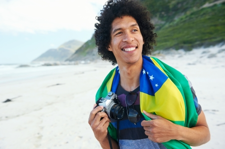 Portrait of happy smiling young Brazilian man with Brasil flag and hipster retro camera at the beach photo