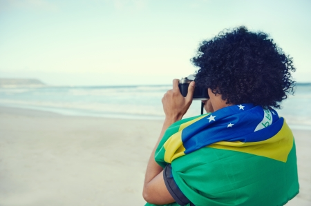 Man with Brasil flag taking photos at the beach photo