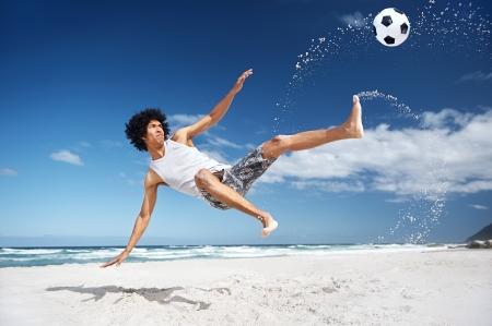 Latino Spaanse mens doet omhaal op het strand met voetbal