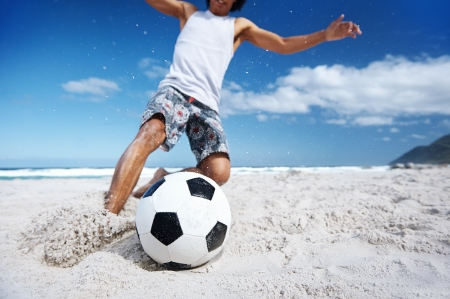 beach man: Hispanic Brasil man playing soccer on beach with dribble skill and ball on vacation Stock Photo