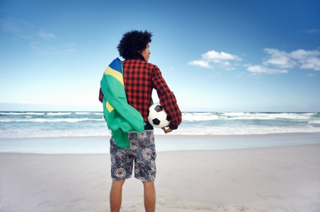 Latino Brasil football soccer fan with flag and ball on beach photo