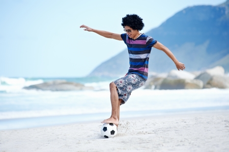 dribble: Hispanic Brasil man playing soccer on beach with dribble skill and ball on vacation Stock Photo