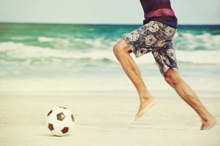 Hispanic Brasil man playing soccer on beach with dribble skill and ball on vacation photo