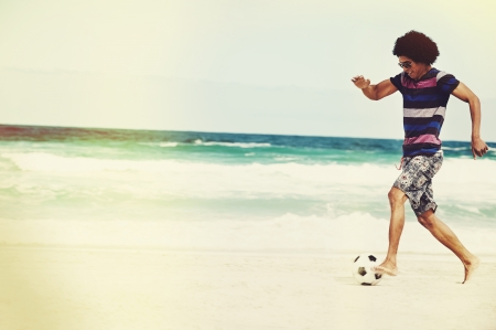 Hispanic Brasil man playing soccer on beach with dribble skill and ball on vacation Stock Photo