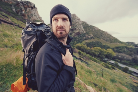 Potrait of adventure trekking man in mountains with backpack photo