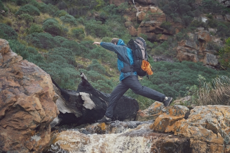 Adventure man crossing river on extreme hike in mountains alone photo