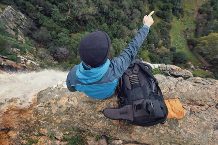 Man sitting on cliff edge looking at vie on outdoor lifestyle adventure hike photo