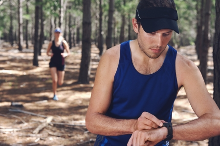 watch movement: Trail running couple check time on their gps watch for tracking pace