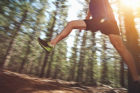 Runner jumping on trail run in forest for marathon fitness photo