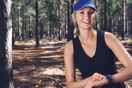 Woman runner checking pace on gps sports watch in forest photo