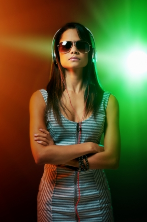 DJ woman portrait with headphones and nightclub lights photo
