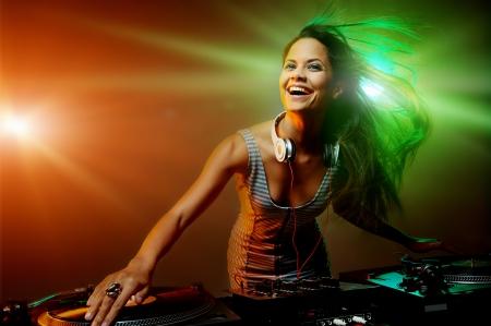 Cute dj žena baví hrát hudbu na vinyl záznam palubě v klubu strana nočního života