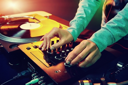 Dj hands on equipment deck and mixer with vinyl record at party photo