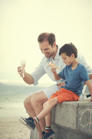 melting: Father and son eating icecream together at the beach on vacation having fun with melting mess