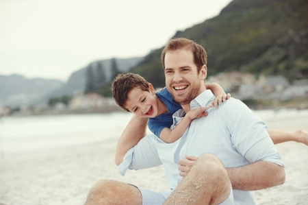 Fatehr en zoon spelen op strand samen portret gelukkig leven plezier