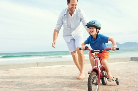 father's: Father and son learning to ride a bicycle at the beach having fun together