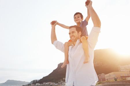 Семья: Сын на плечи отцов на пляже весело на закате вместе