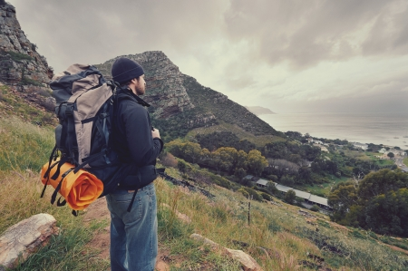 Adventure man hiking wilderness mountain with backpack, outdoor lifestyle survival vacation photo