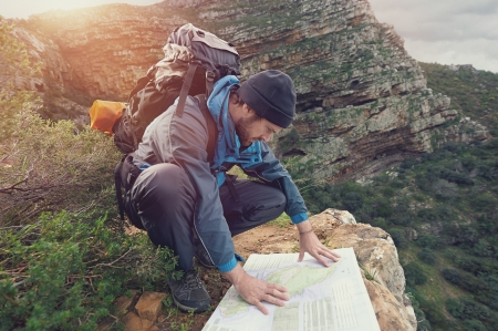 survive: Lost hiker with backpack checks map to find directions in wilderness area Stock Photo