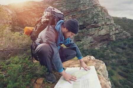 Verloren wandelaar met rugzak controles in kaart om aanwijzingen te vinden in de wildernis gebied