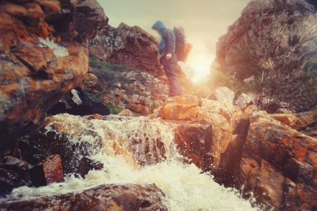 Survival man crossing river in mountains with backpack, sunrise or sunset and danger photo